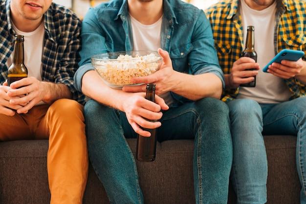 Sección media de tres hombres sentados juntos en un sofá sosteniendo botellas de cerveza en la mano
