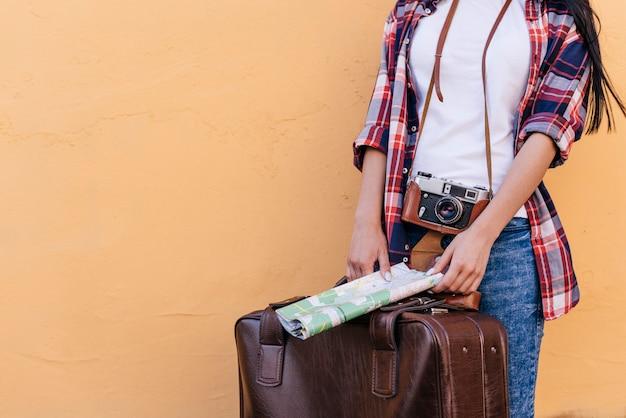 Sección media del viajero femenino que sostiene el mapa y la bolsa de equipaje con la cámara de pie cerca de la pared de melocotón