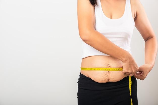 Sección de uso de la mujer cicatriz posparto que mide la cintura marca de estiramiento piel del abdomen inferior flojo ella gorda después del embarazo nacimiento del bebé