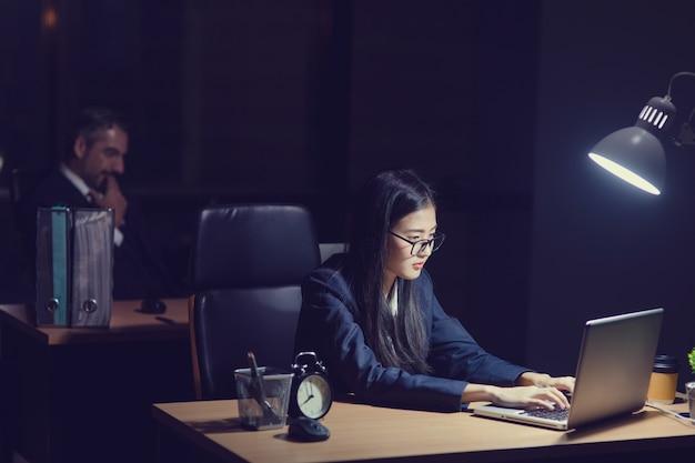 Secretaria asiática chica trabajando hasta tarde sentado en el escritorio en la oficina por la noche. mujer de negocios escribiendo en la computadora portátil frente a su jefe gerente jefe caucásico