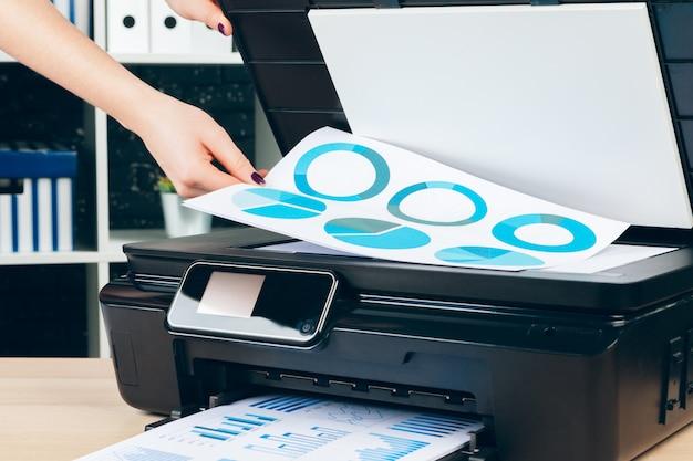 Secretaria femenina haciendo fotocopias en la máquina xerox en la oficina