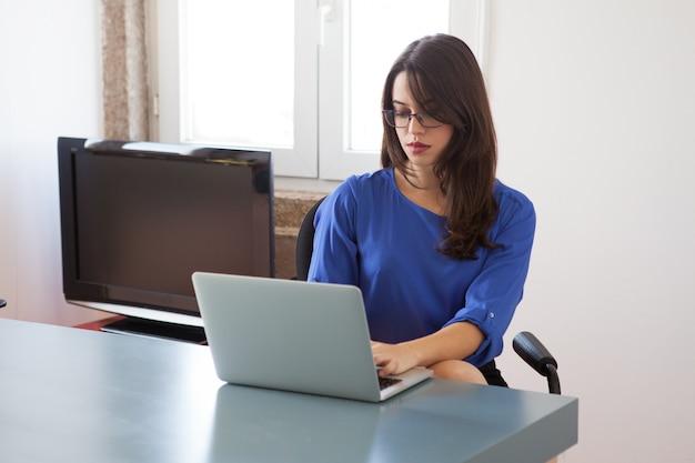 Secretaria ocupada preparando informe en la computadora portátil