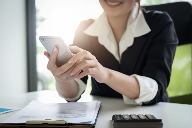 Secretaria de sexo femenino joven que sostiene el teléfono para el horario de la reunión del cliente del contacto
