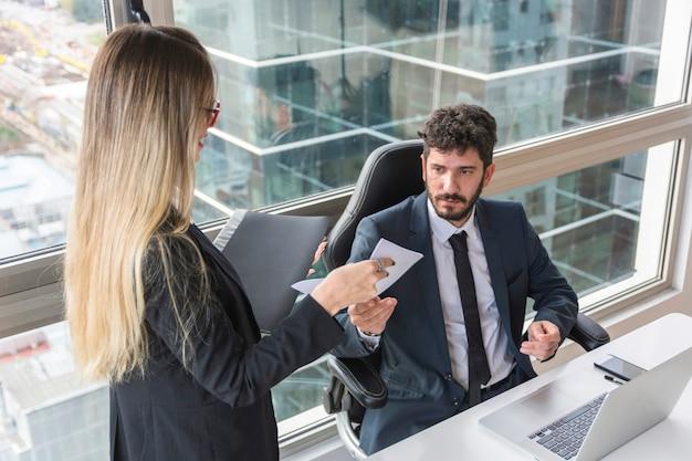 Secretaria de sexo femenino que da el documento al encargado masculino en el lugar de trabajo