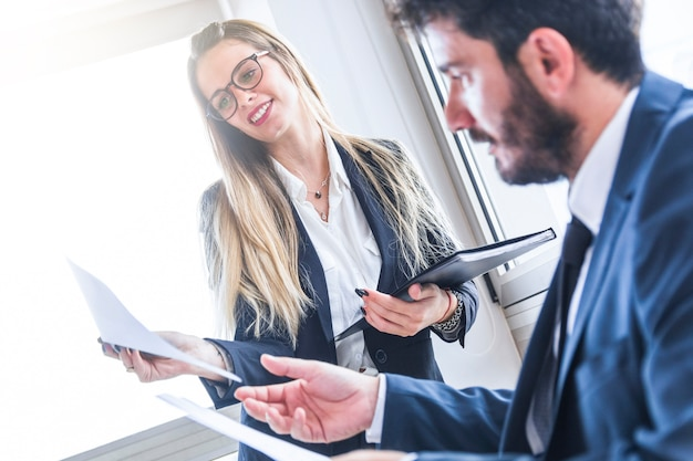 Secretaria de sexo femenino sonriente que muestra el documento al encargado masculino