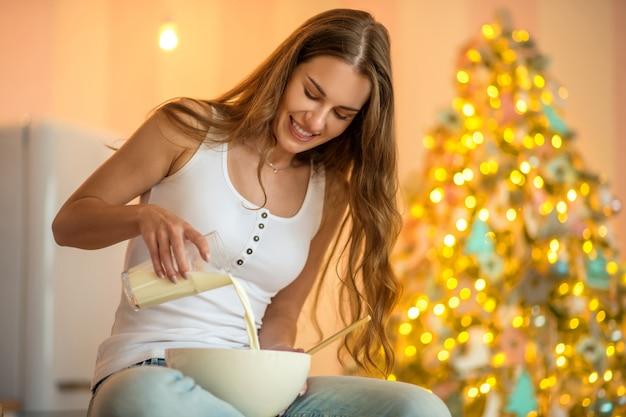Secretos de cocina. mujer bonita en camiseta blanca vertiendo leche