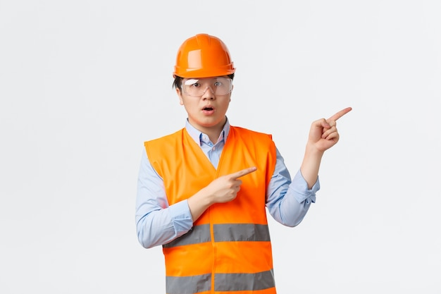 Sector de la construcción y concepto de trabajadores industriales. gerente de construcción asiático impresionado y asombrado, ingeniero con casco y ropa reflectante apuntando hacia la esquina superior derecha, pared blanca