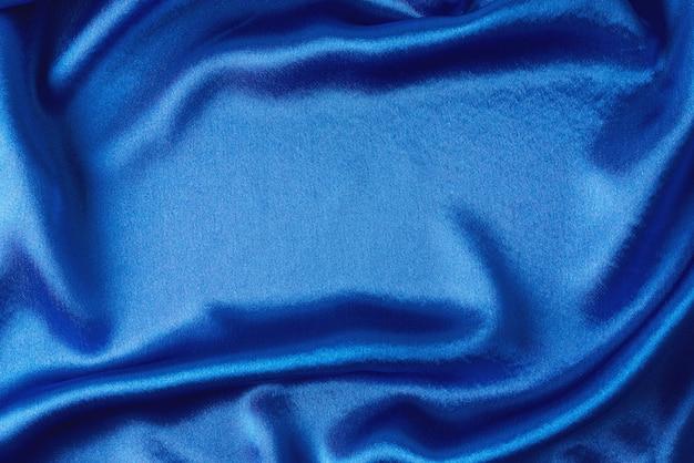 Seda azul con pliegues. textura abstracta de superficie satinada ondulada