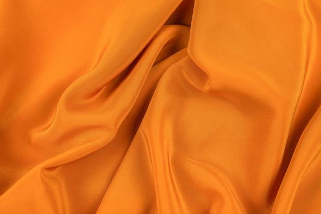 La seda dorada o la textura de tela de lujo satinada se pueden utilizar como fondo abstracto.
