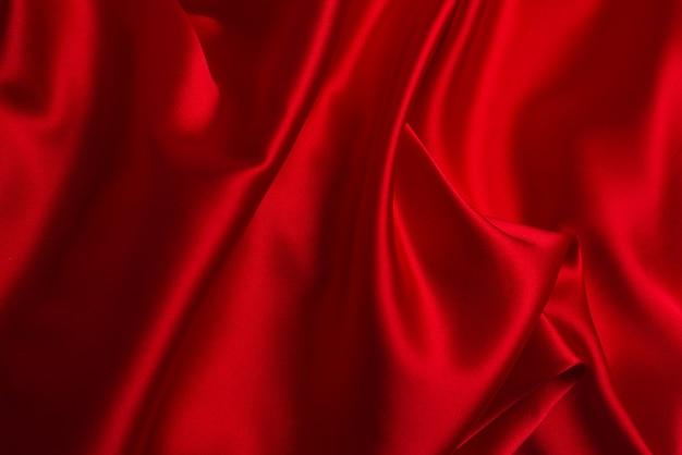 La seda roja o la textura de lujo de la tela del satén pueden utilizar como fondo abstracto.