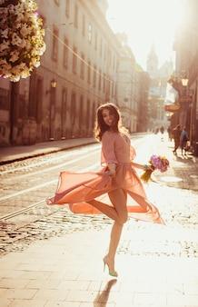 Seductora joven en vestido ligero giros en la luz de la mañana