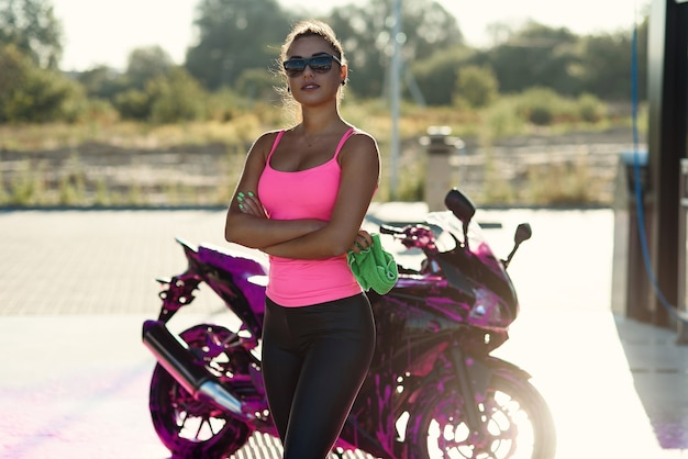 Seductora mujer joven en camiseta rosa posa cerca de una motocicleta deportiva en el autoservicio de lavado de autos por la mañana.