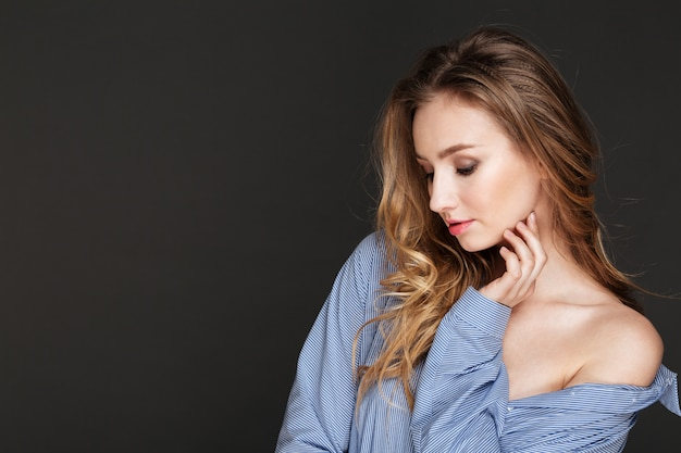 Seductora mujer joven encantadora con cabello rubio rizado