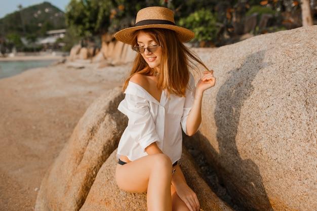 Seductora mujer rubia en blusa blanca posando en playa tropical