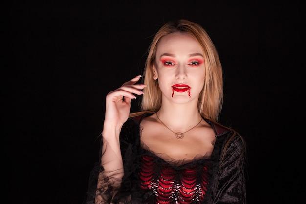 Seductora mujer rubia vestida como vampiro para halloween.
