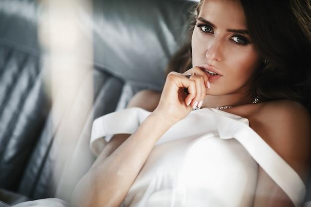 Seductora novia sentada dentro de un auto retro blanco con asientos de cuero