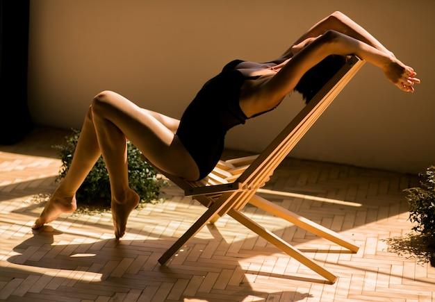 Seductora piensa mujer con piernas largas posa en una lencería en los rayos del sol de la mañana