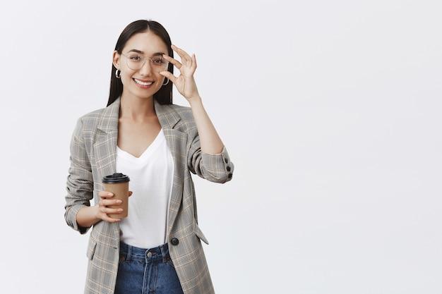 Segura y alegre mujer guapa con gafas y elegante chaqueta, tocando el borde y sonriendo ampliamente mientras sostiene una taza de café, bebiendo bebidas