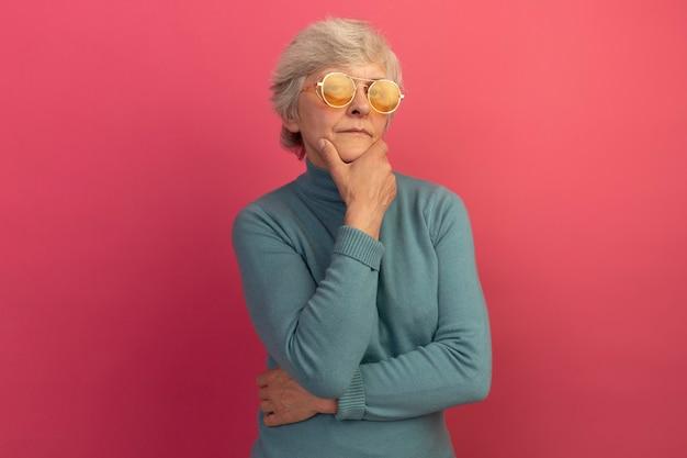 Segura anciana vestida con un suéter de cuello alto azul y gafas de sol manteniendo la mano en la barbilla mirando al frente aislado en la pared rosa con espacio de copia