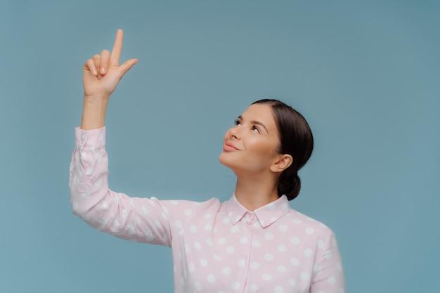 Segura apuesto elegante mujer señala arriba en espacio libre