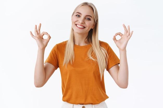 Segura de guapa mujer rubia moderna con tatuajes en camiseta naranja, sonriendo despreocupada y positiva, dar aprobación, mostrar bien, firmar ok, aceptar la elección perfecta, de pie fondo blanco