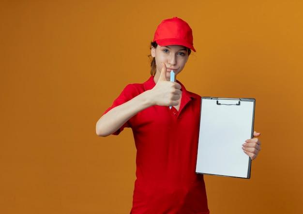 Segura joven bonita repartidora en uniforme rojo y gorra sosteniendo bolígrafo y portapapeles y mostrando el pulgar hacia arriba en cámara aislada sobre fondo naranja con espacio de copia