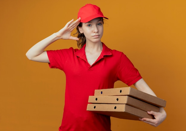 Segura joven bonita repartidora en uniforme rojo y gorra sosteniendo paquetes de pizza y haciendo gesto de saludo aislado sobre fondo naranja