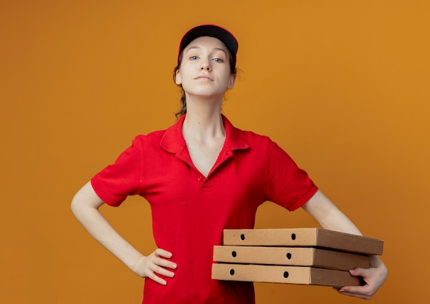 Segura joven bonita repartidora en uniforme rojo y gorra sosteniendo paquetes de pizza y poniendo la mano en la cintura mirando a cámara aislada sobre fondo naranja