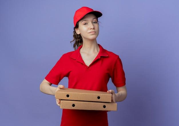 Segura joven bonita repartidora vestida con uniforme rojo y gorra sosteniendo paquetes de pizza aislado sobre fondo púrpura con espacio de copia
