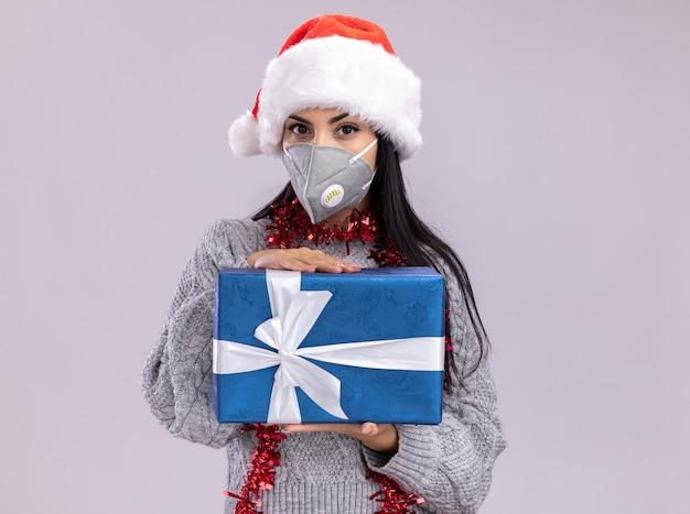 Segura joven caucásica con sombrero de navidad y guirnalda de oropel alrededor del cuello con máscara protectora mirando a cámara sosteniendo paquete de regalo aislado sobre fondo blanco con espacio de copia