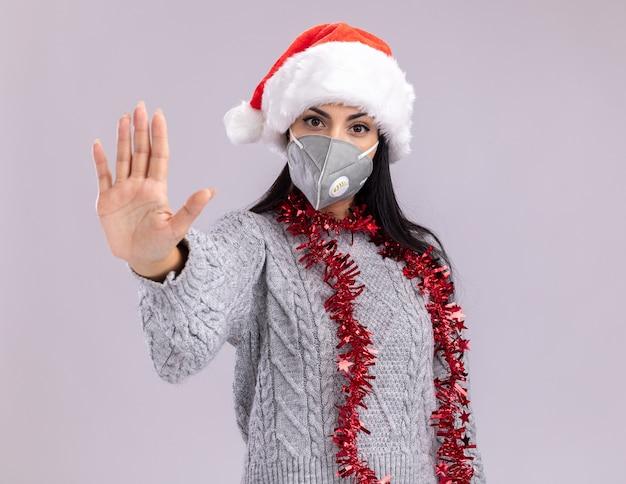 Segura joven caucásica vistiendo gorro de navidad y guirnalda de oropel alrededor del cuello con máscara protectora mirando a cámara haciendo gesto de parada aislado sobre fondo blanco con espacio de copia