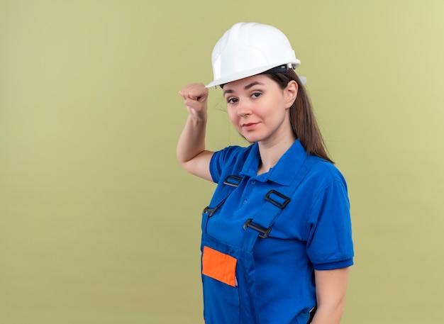 Segura joven constructora con casco de seguridad blanco y uniforme azul levanta el puño y mira a la cámara sobre fondo verde aislado con espacio de copia