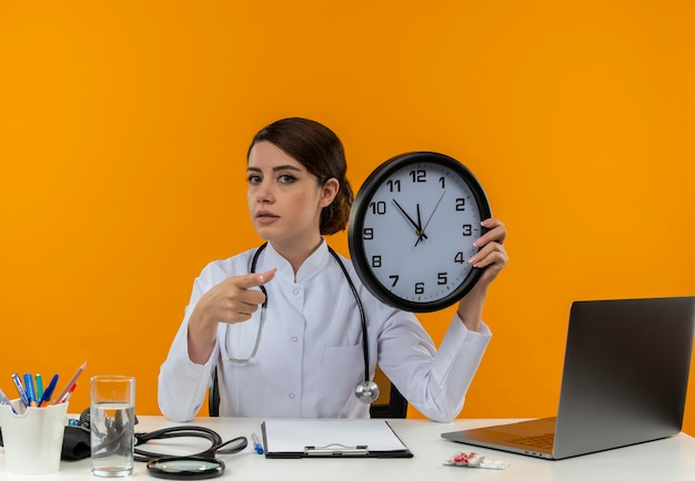 Segura joven doctora vistiendo bata médica y estetoscopio sentado en el escritorio con herramientas médicas y portátil con reloj apuntando aislado en la pared amarilla