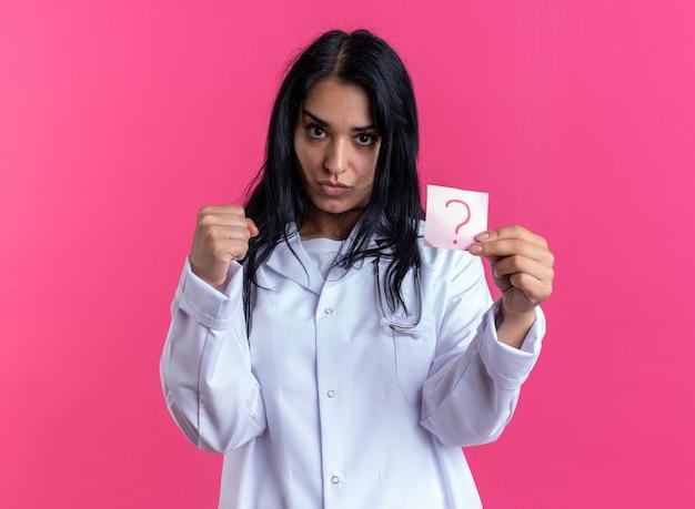 Segura joven doctora vistiendo bata médica con estetoscopio sosteniendo papel de nota en signo de interrogación aislado en la pared rosa