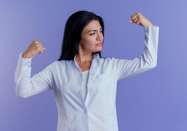 Segura joven doctora vistiendo bata médica haciendo un gesto fuerte y mirando sus músculos