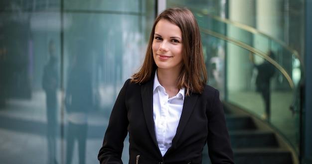 Segura joven gerente femenina al aire libre en un entorno urbano moderno