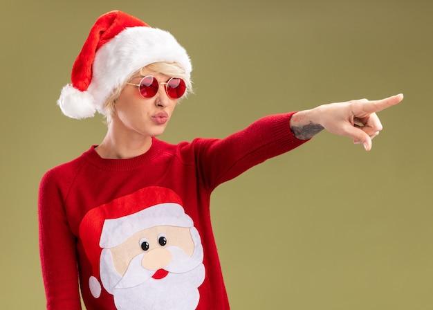 Segura joven rubia con sombrero de navidad y suéter de navidad de santa claus con gafas mirando y apuntando al lado con los labios fruncidos aislados sobre fondo verde oliva