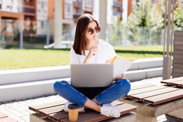 Segura mujer atractiva sentada en el banco en el parque y mensajes en las redes sociales mientras escribía en el cuaderno durante el descanso para tomar café