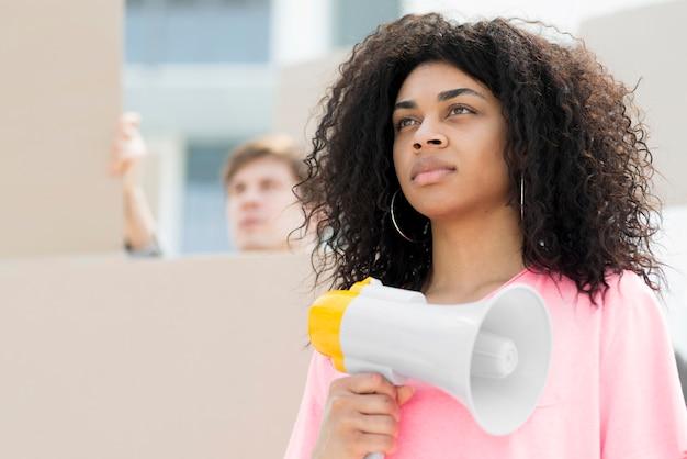 Segura mujer con cabello rizado protestando