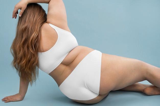Segura mujer de gran tamaño posando en lencería blanca