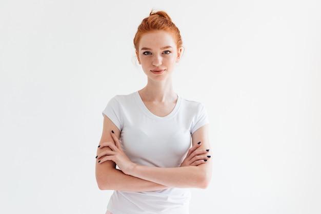 Segura mujer de jengibre en camiseta posando con los brazos cruzados y mirando