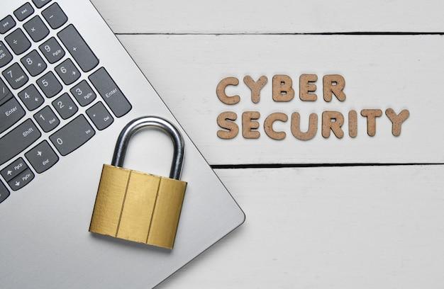 La seguridad cibernética. portátil y candado en madera blanca