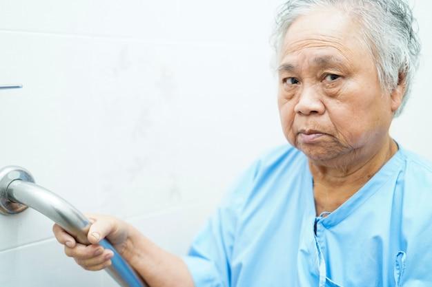 Seguridad mayor asiática o mayor de la manija del retrete del uso paciente de la mujer de la señora mayor en hospital de enfermería.