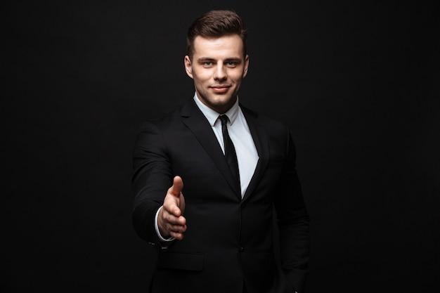 Seguro atractivo joven empresario vistiendo traje que se encuentran aisladas sobre la pared negra, sosteniendo la mano extendida para saludar