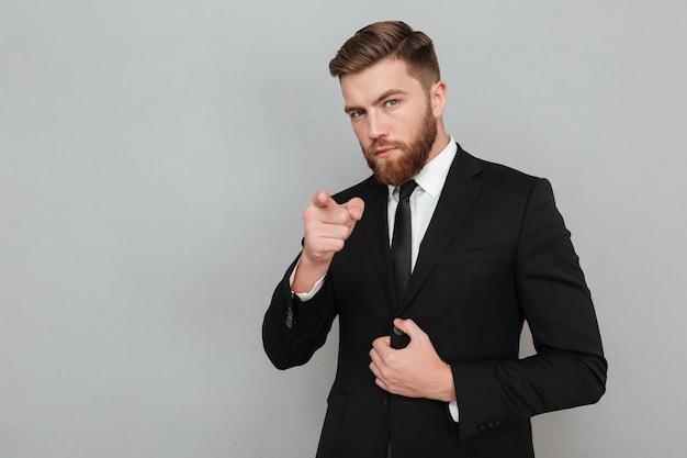Seguro empresario guapo en traje de señalar con dedo