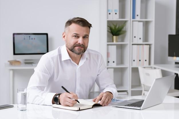 Seguro empresario maduro sentado por el escritorio en su oficina mientras escribe el plan de trabajo en el cuaderno