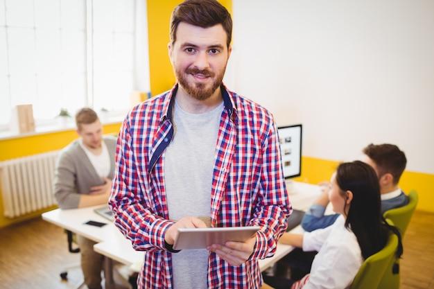 Seguro empresario con tableta en oficina creativa