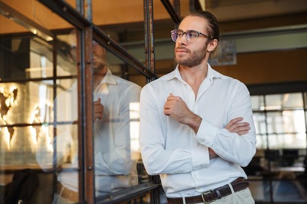 Seguro hombre caucásico en anteojos mirando a un lado mientras se inclina sobre la pared de cristal en la oficina moderna