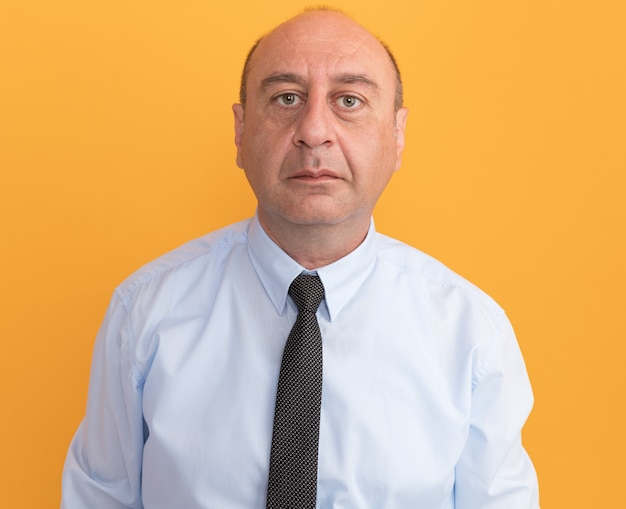 Seguro de hombre de mediana edad vestido con camiseta blanca con corbata aislado en la pared naranja