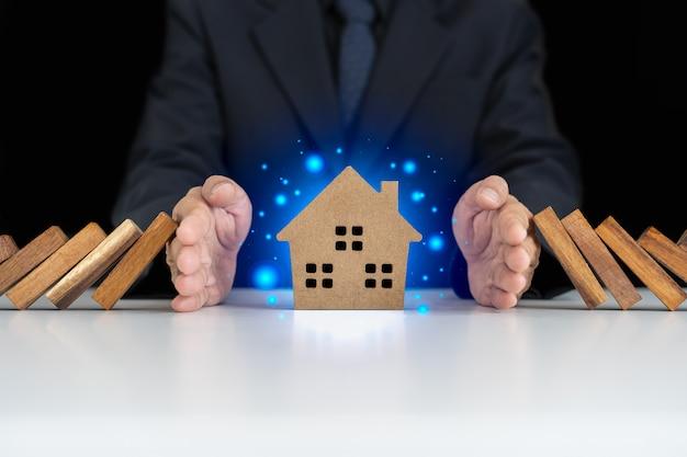 El seguro con las manos protege una casa seguro de hogar o concepto de seguro de casa